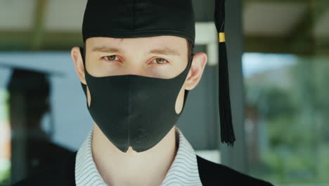 Portrait-Of-A-Graduate-In-A-Robe-And-Cap-With-A-Protective-Mask-On-His-Face
