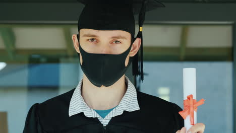 The-Graduate-Holds-A-Diploma-In-His-Hand-Wearing-A-Robe-And-Cap-With-A-Protective-Mask-On-His-Face