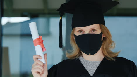 A-Female-Graduate-In-A-Mask-Holds-A-Diploma-In-Her-Hand