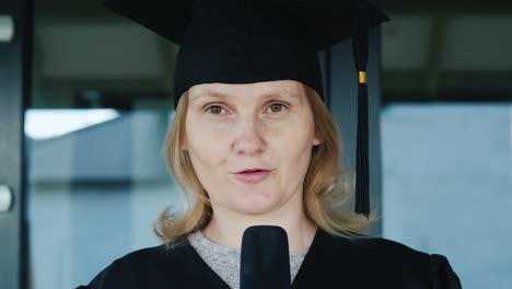 A-Graduate-In-A-Robe-And-Cap-Speaks-Into-The-Microphone