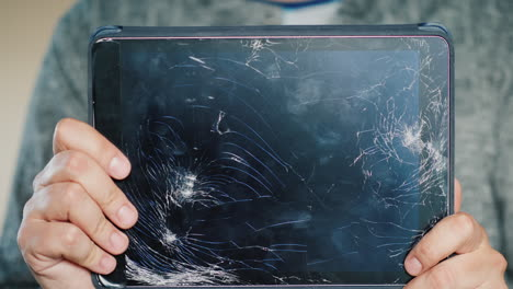 A-Man-Holds-A-Tablet-With-A-Broken-Screen