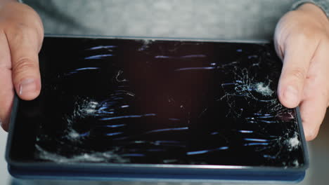 A-Man-Holds-A-Tablet-With-A-Broken-Screen-1