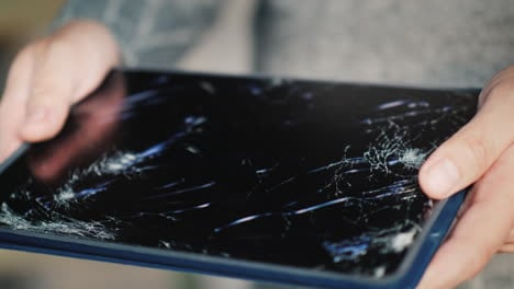 A-Man-Holds-A-Tablet-With-A-Broken-Screen-2