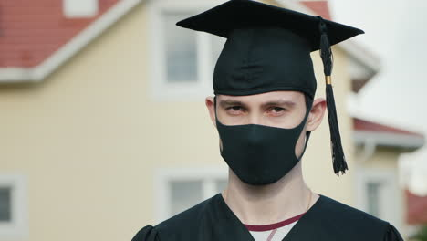 Portrait-Of-A-Graduate-In-A-Protective-Mask-Wearing-A-Robe-And-A-Graduate-Cap-1