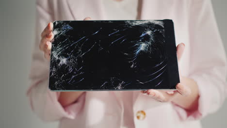 A-Woman-Holds-A-Tablet-With-A-Broken-Screen
