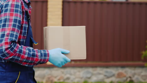 Side-View:-A-Courier-With-A-Parcel-Of-Hands-Walks-Along-The-Street