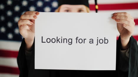 A-Graduate-In-A-Mantle-And-Cap-Is-Holding-A-Poster-About-Job-Employment