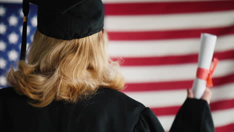 Graduate-With-A-Diploma-Against-The-Background-Of-The-Us-Flag