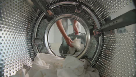 A-woman-puts-white-laundry-in-the-washing-machine