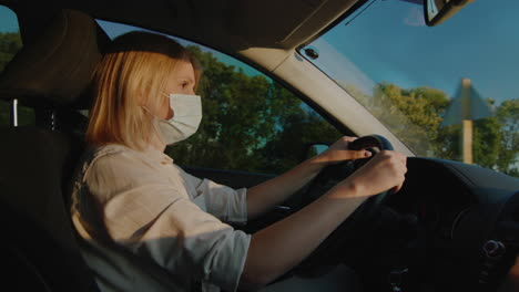 Driver-in-protective-mask-drives-behind-the-wheel-of-a-car