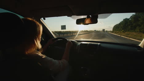 Middle-aged-female-driver-drives-car-in-setting-sun-4
