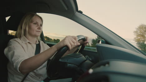 Middle-aged-female-driver-drives-car-in-setting-sun-6