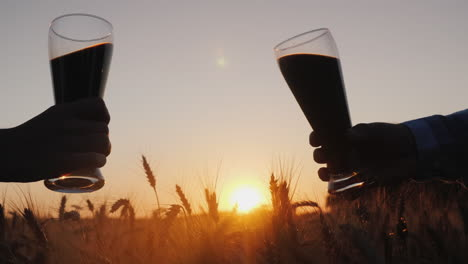 Hands-with-bottles-of-beer-clink-against-the-background-of-a-wheat-field-3