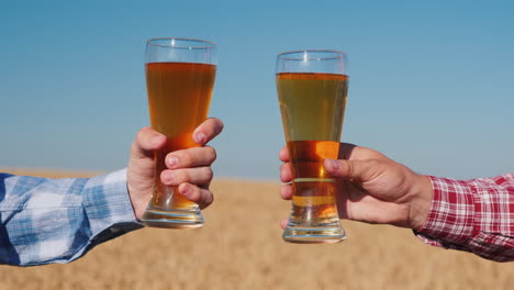 Hands-with-glasses-of-beer-clink-glasses-in-a-wheat-field