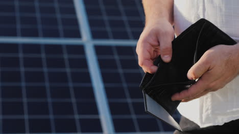 A-Man-Holds-An-Empty-Purse-Against-The-Background-Of-Solar-Panels