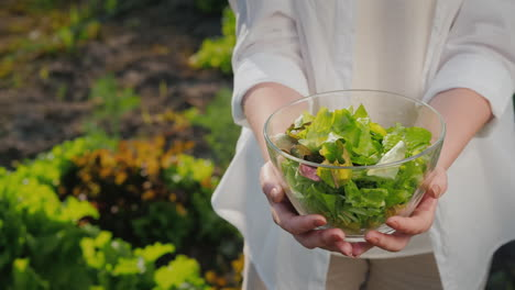 A-Woman-Holds-A-Bowl-Of-Lettuce-On-The-Background-Of-Her-Garden