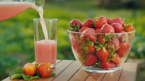 Pour-The-Juice-Into-A-Glass-Next-To-A-Plate-Of-Fresh-Strawberries-1
