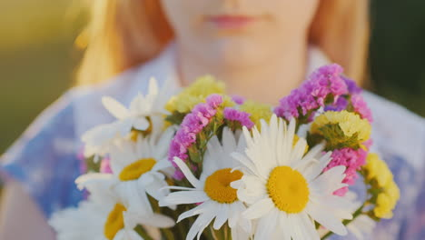 Blonde-girl-holds-a-bouquet-of-flowers-stands-in-a-meadow-at-sunset