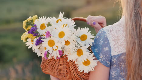 A-child-holds-a-basket-of-flowers-stands-in-a-meadows-and-green-hills