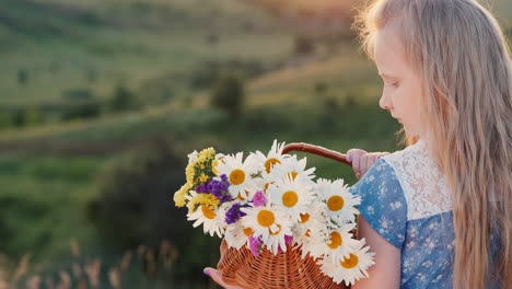 A-child-holds-a-basket-of-flowers-stands-in-a-meadows-and-green-hills-1