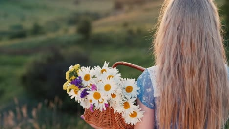 A-child-holds-a-basket-of-flowers-stands-in-a-meadows-and-green-hills-2