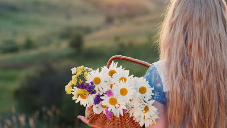 A-child-holds-a-basket-of-flowers-stands-in-the-green-hills
