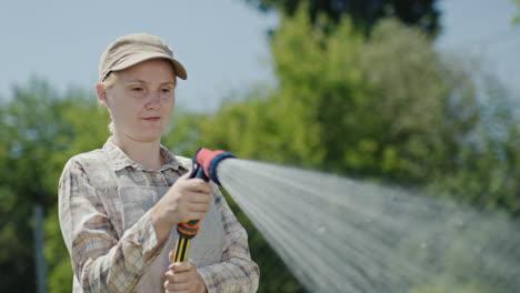 Gardener-sprays-water-from-a-garden-hose-3