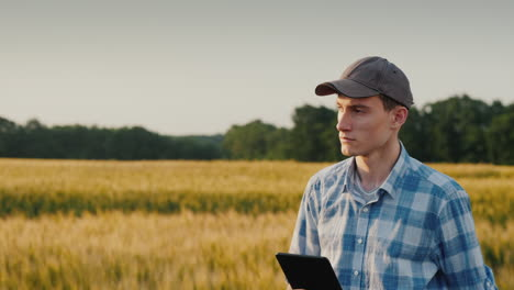 A-Young-Farmer-With-A-Tablet-In-His-Hand-Walks-Along-A-Wheat-Field