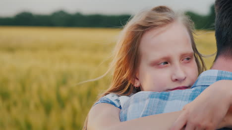 The-Child-Clings-To-His-Father-s-Shoulder-In-The-Background-A-Strong-Wind-Swaying-Wheat