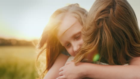 A-Girl-Hugs-Her-Mother-In-The-Background-Of-A-Field-Where-The-Wind-Sways-Wheat