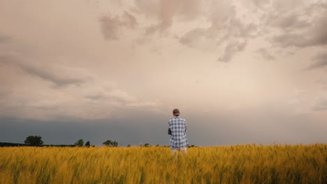 A-Young-Farmer-Stands-Alone-In-A-Field-Of-Wheat-Against-A-Stormy-Sky