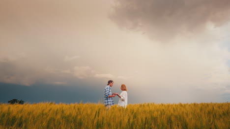 Two-Farmers-Stand-In-A-Field-Of-Wheat-Against-A-Stormy-Sky-2