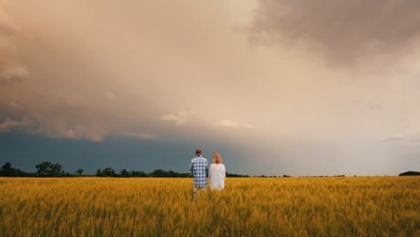 A-Man-And-A-Woman-Stand-In-A-Field-Of-Wheat-Against-A-Stormy-Sky-Where-Lightning-Is-Visible
