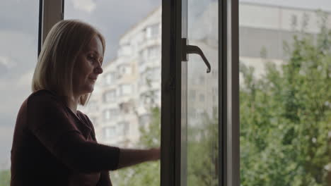 A-woman-washes-a-window-in-the-apartment-of-a-high-rise-building-2
