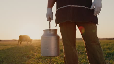 A-farmer-with-a-milk-can-stands-in-a-meadow-where-a-cow-grazes