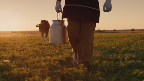 Farmer-pours-milk-into-can-at-sunset-3