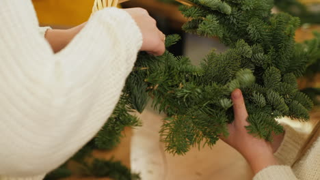 Woman-and-baby-make-Christmas-wreath-from-conifers