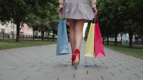 Woman-in-summer-short-dress-carries-packages-with-fashionable-shopping