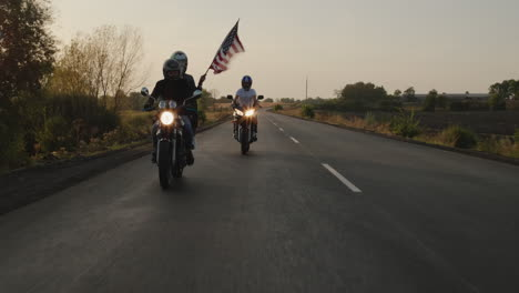 Silhouettes-of-bikers-ride-on-the-highway-at-sunset-with-the-American-flag