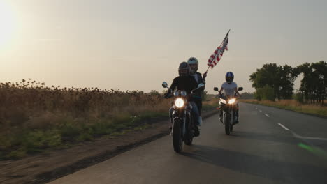 A-group-of-young-men-rides-motorcycles-at-sunset