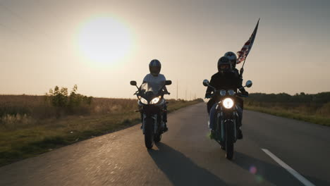 A-pair-of-bikers-travels-on-a-motorcycle-followed-by-an-American-flag-1