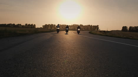 Three-bikers-drive-along-the-highway-past-the-camera