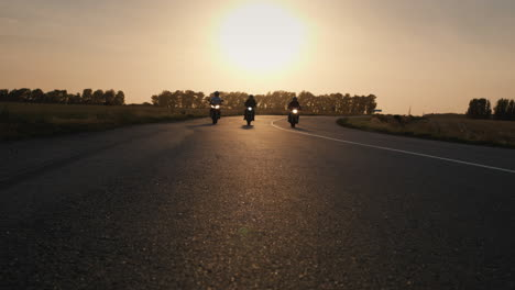 Three-bikers-drive-along-the-highway-past-the-camera-1