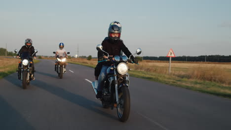 A-group-of-bikers-drives-along-the-highway-among-the-fields-on-a-clear-autumn-day
