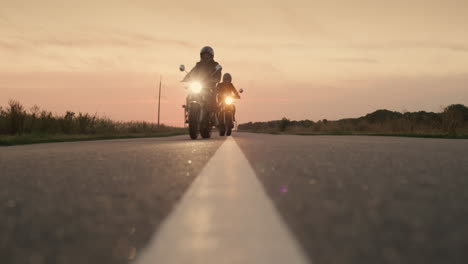Two-motorcycles-drive-on-a-flat-highway-at-sunset-1