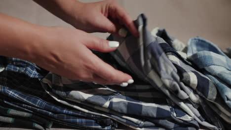 Women-s-hand-smooth-men-s-shirts-folded-on-the-shelf