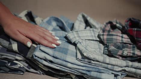 Women-s-hand-smooth-men-s-shirts-folded-on-the-shelf-1