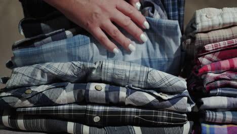 Women-s-hands-sort-through-a-stack-of-men-s-shirts