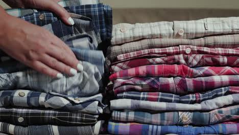 Women-s-hands-sort-through-a-stack-of-men-s-shirts-1
