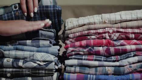 Women-s-hands-sort-through-a-stack-of-men-s-shirts-2